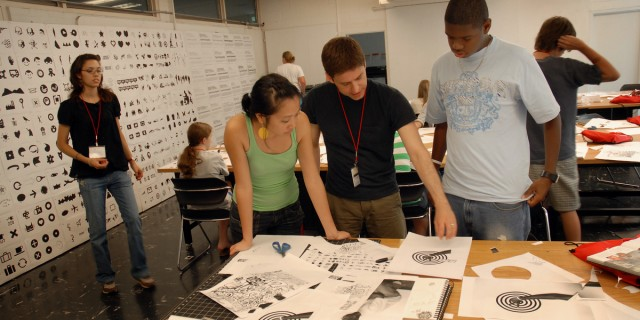 Design Camp instructor looks over students' work during class in Brooks Hall. PHOTO BY ROGER WINSTEAD